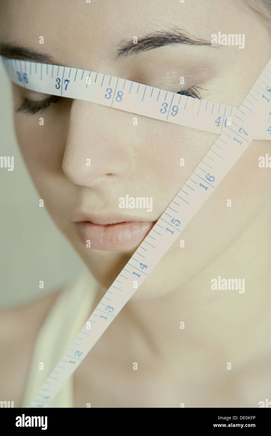 Woman with measuring tape wrapped across face, eyes closed - Stock Image