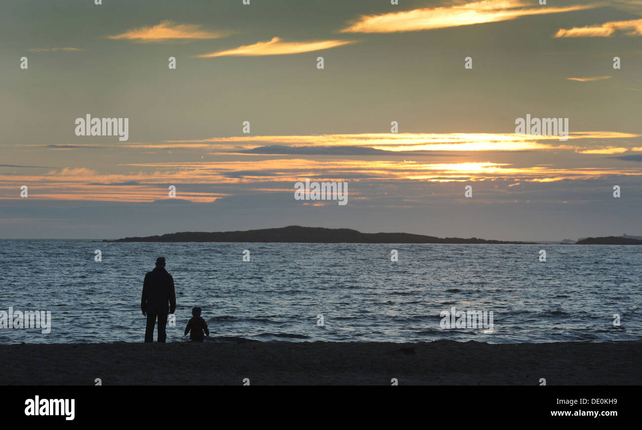 MAN AND SMALL CHILD LOOK OUT TO SUNSET ON BEACH RE FAMILY BREAKUP DIVORCE SINGLE PARENT COASTAL FAMILIES PARENTS RELATIONSHIP - Stock Image