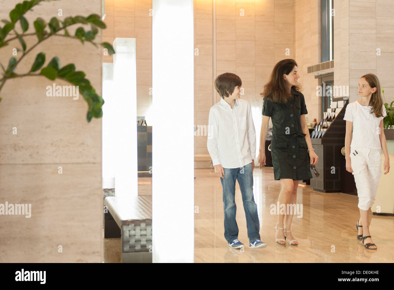 Mother and children walking in hotel lobby - Stock Image