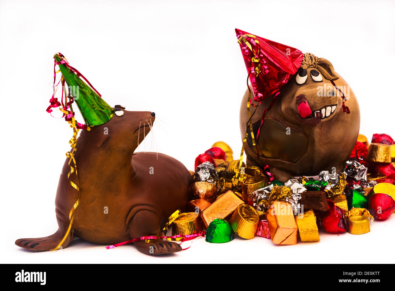 Two clay animals in a party. Happy cow on a chocolate high, disapproving sea lion, standing on a pile of bonbons and wrappers, - Stock Image