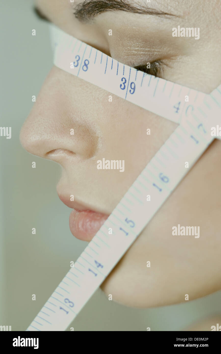 Woman with measuring tape wrapped across face, close-up - Stock Image
