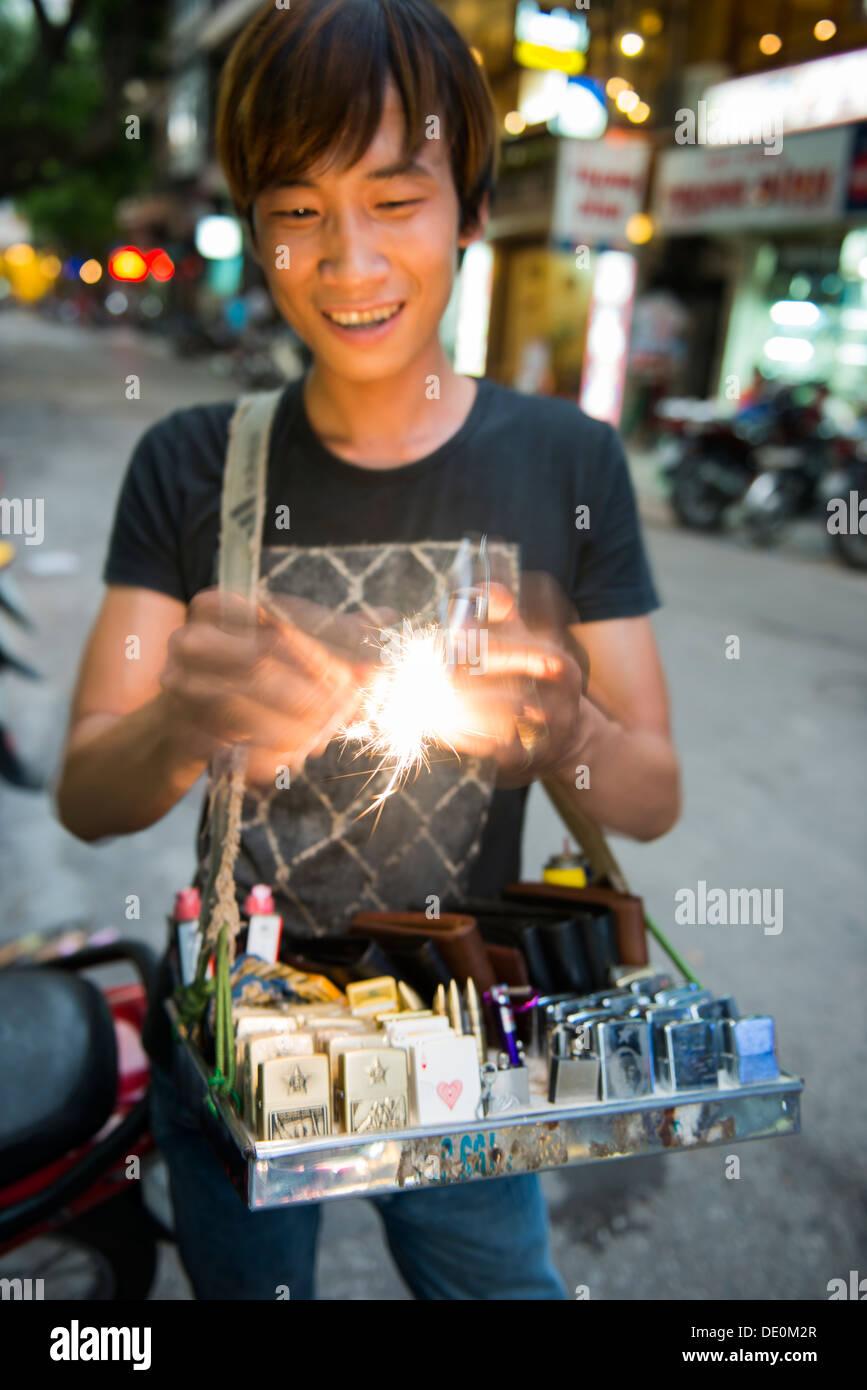 Cigarette lighter paddling seller showing flint and firestone lighter on the Hanoi street, Vietnam - Stock Image