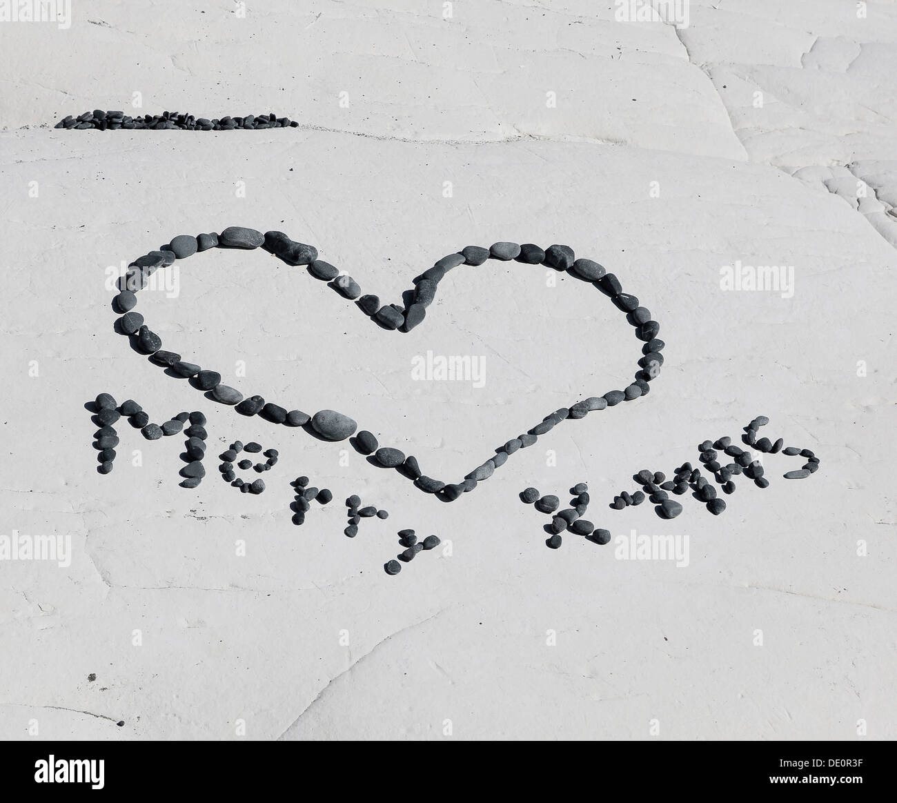Merry X-Mas, made of stones laid on a rock - Stock Image