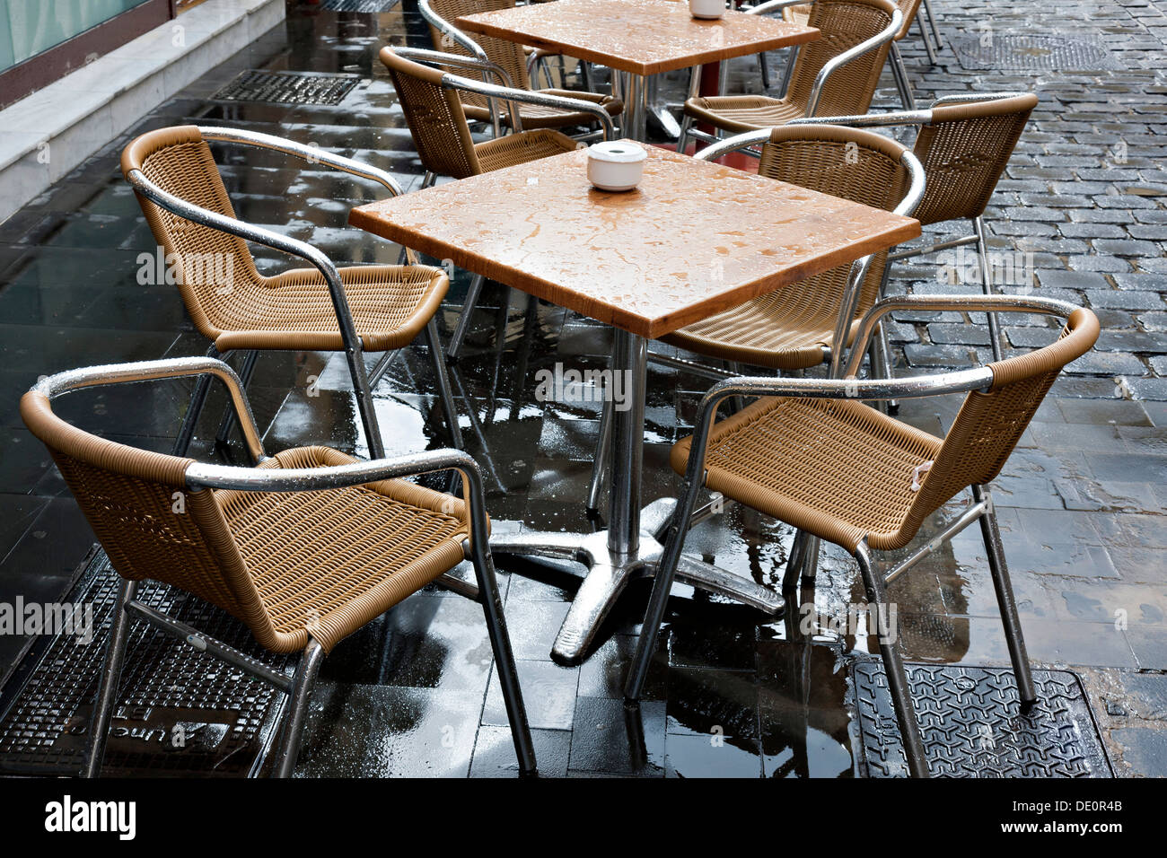 Wet bistro table and chairs, Las Palmas, Gran Canaria, Spain - Stock Image