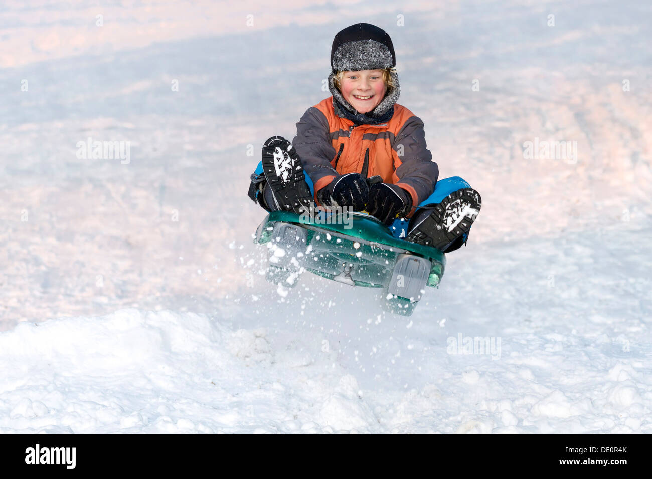 Boy jumping with a sledge - Stock Image
