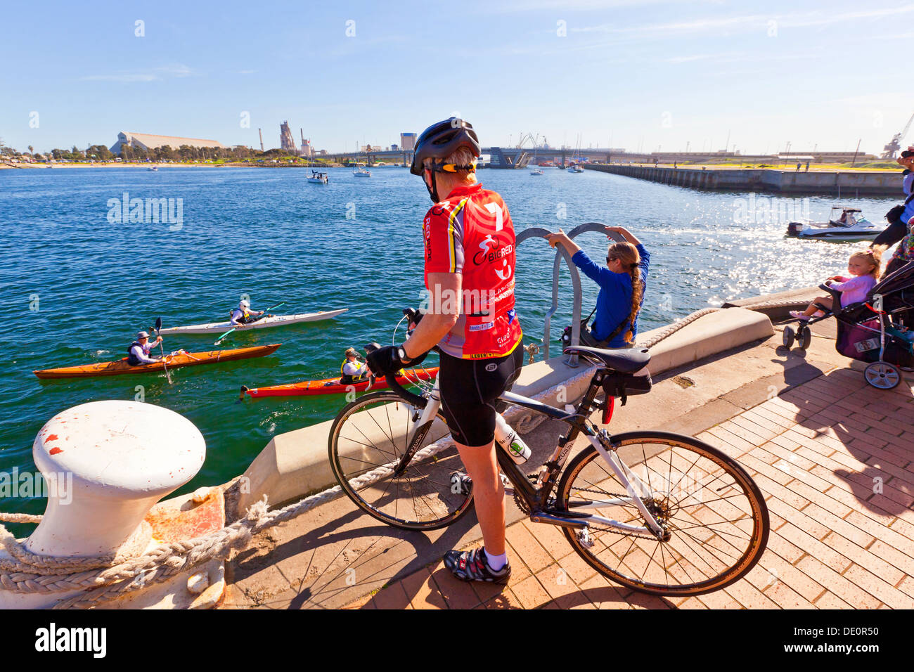 A female cyclist watches people canoing along the Port River at Port Adelaide in South Australia - Stock Image