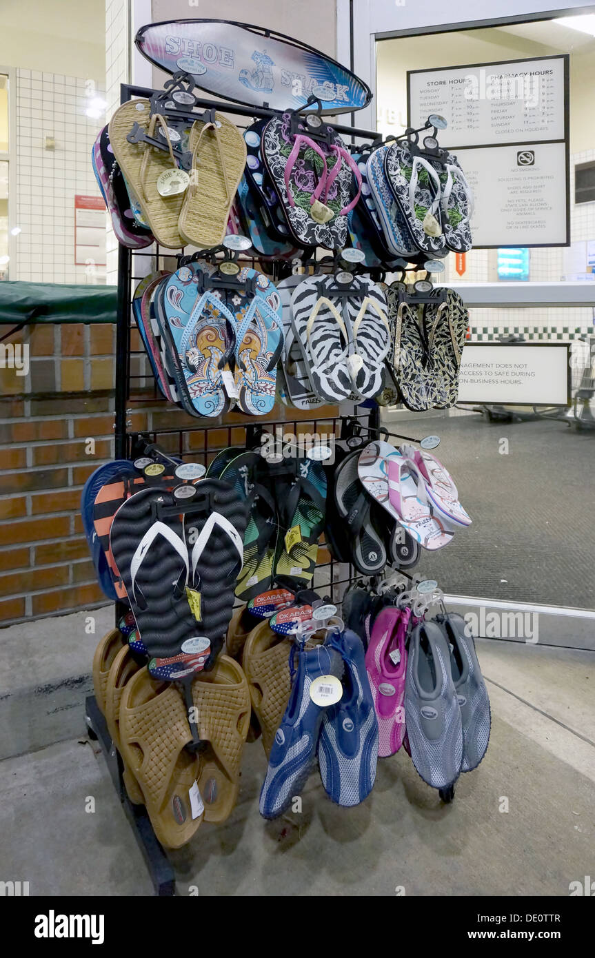 92baf0724b6cdb Colorful flip flops, sandals and beach shoes for sale on a display rack  outside a