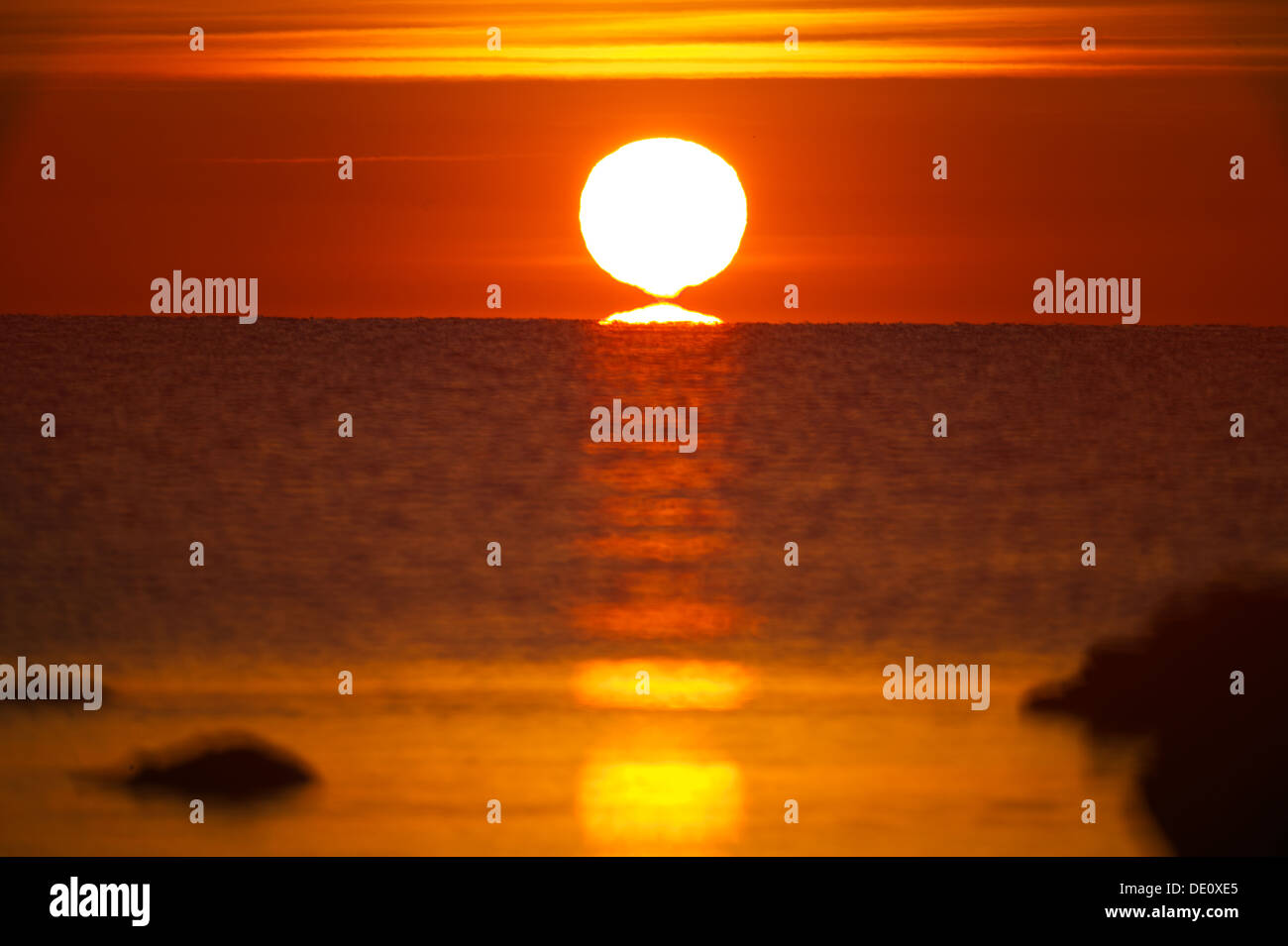 Morning sunrise with clear skies an sun reflecting in the sea. The sun is shaded like an omega - Stock Image