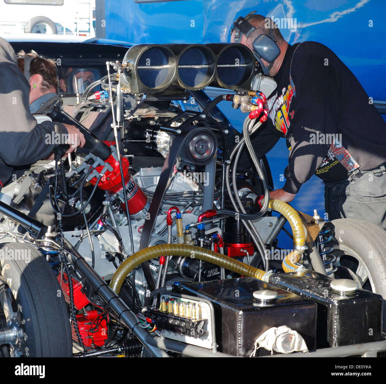 Mechanics checking the ignition timing with a strobe on their Pontiac Firebird Pro Mod dragster at Santa Pod pits. - Stock Image