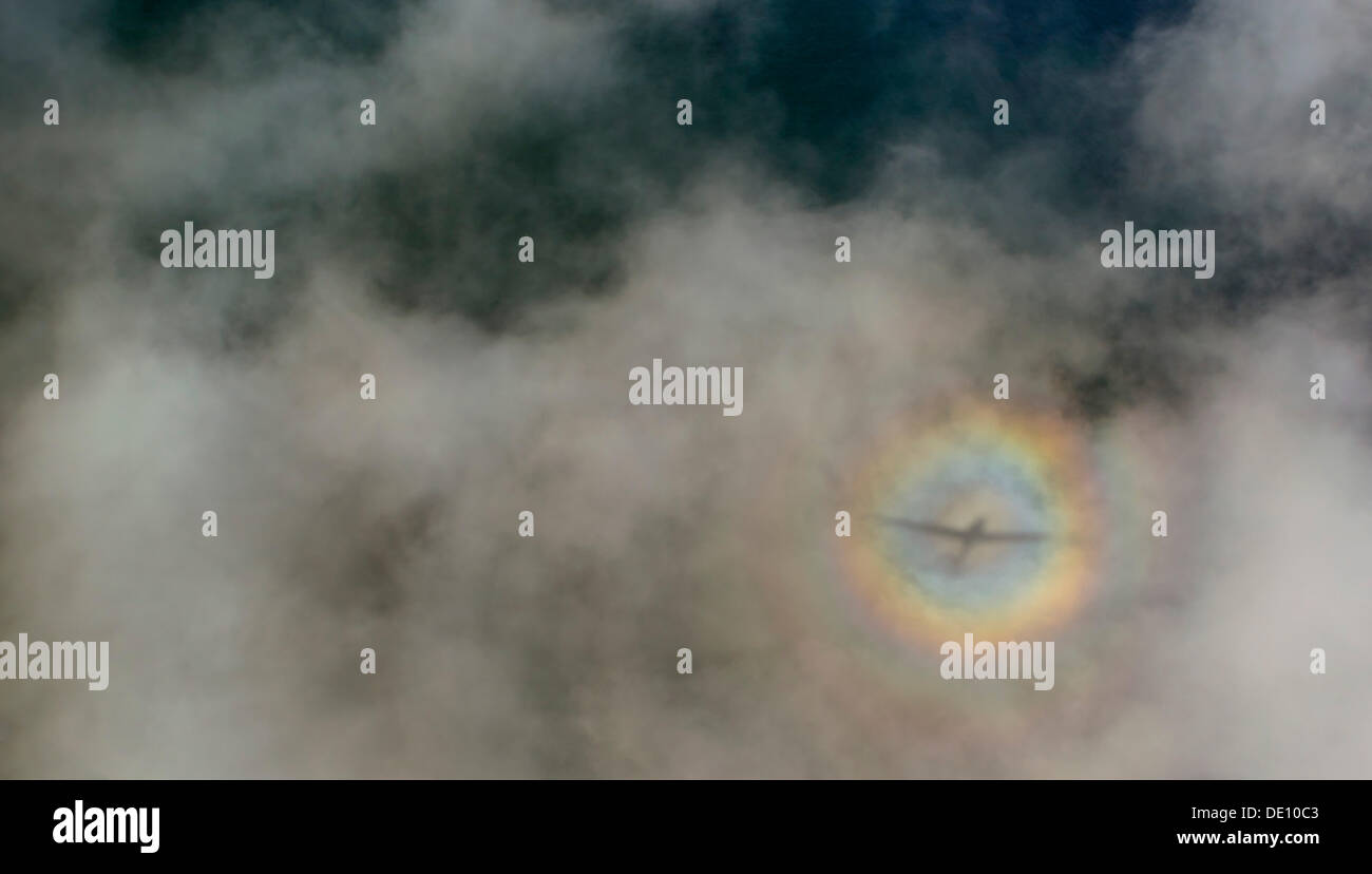 Aerial view, airplane with cloud shadows and diffuse circular rainbow - Stock Image