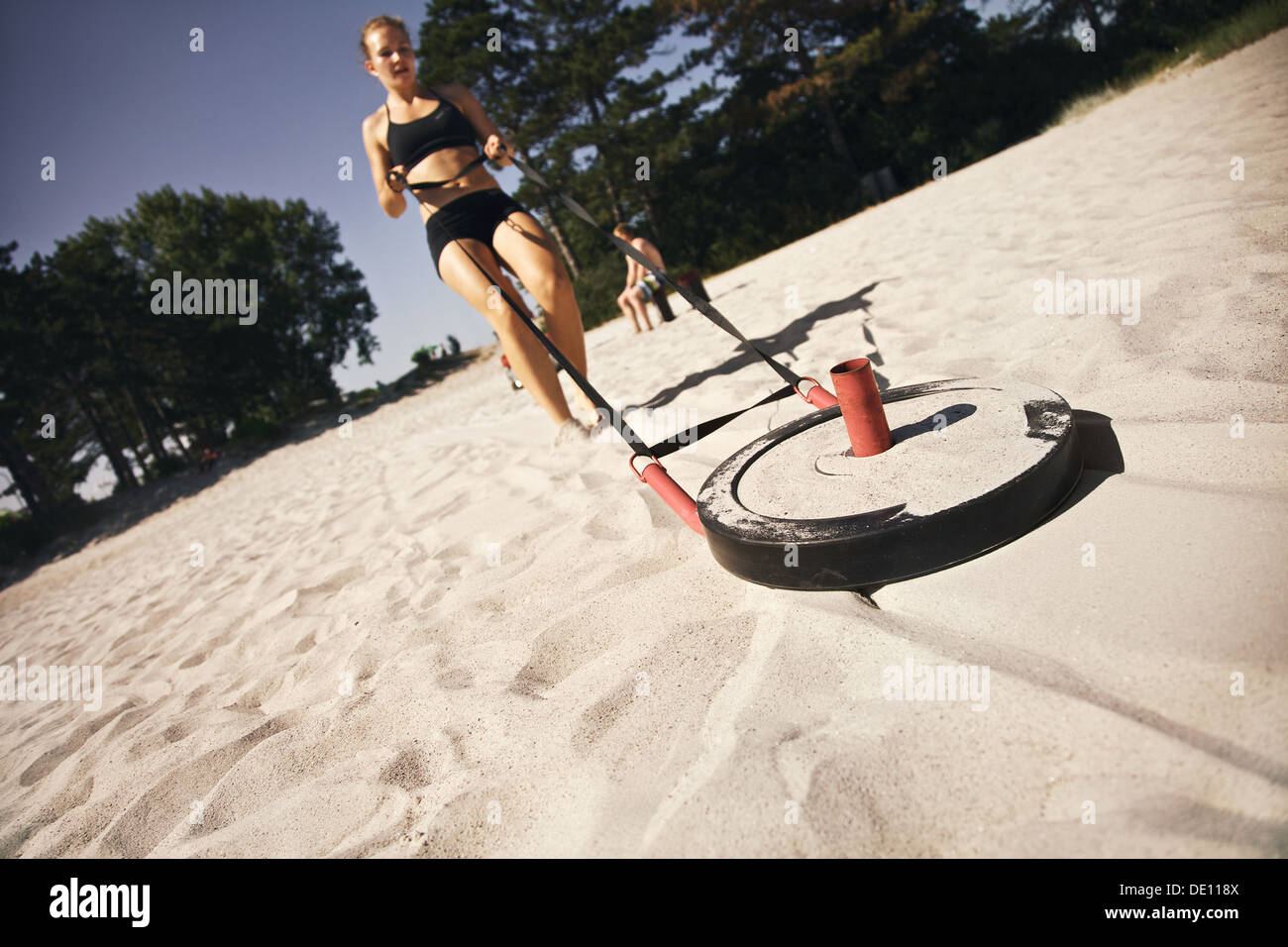 Strong young woman pulling a crossfit sled across a sandy beach outdoors on a hot summer day - Stock Image