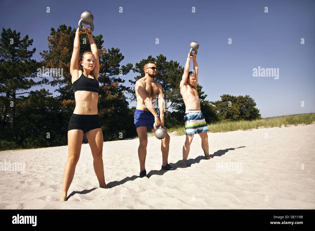 Group of athletes swinging a kettle bell over their head on beach. Young people doing crossfit workout on a hot summer day. - Stock Image