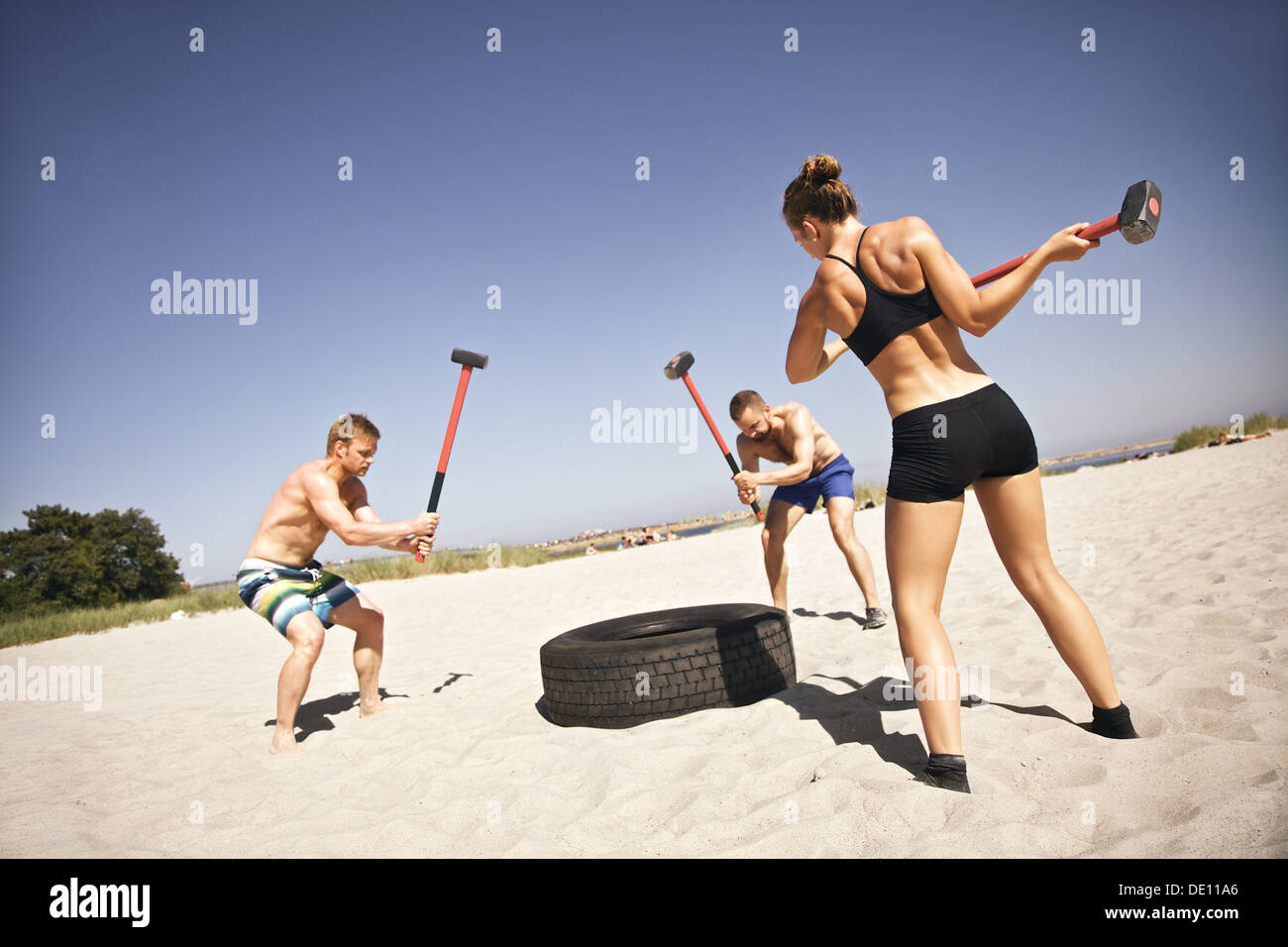 Three strong athletes doing hammer strike on a truck tire during crossfit exercise outside on beach Stock Photo