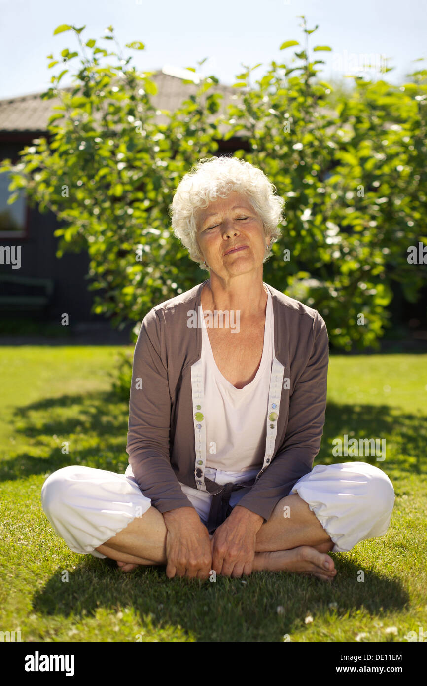 Elder woman sitting on grass with eyes closed in garden outdoors. Meditating in nature in yoga position. Calm and relaxed. - Stock Image