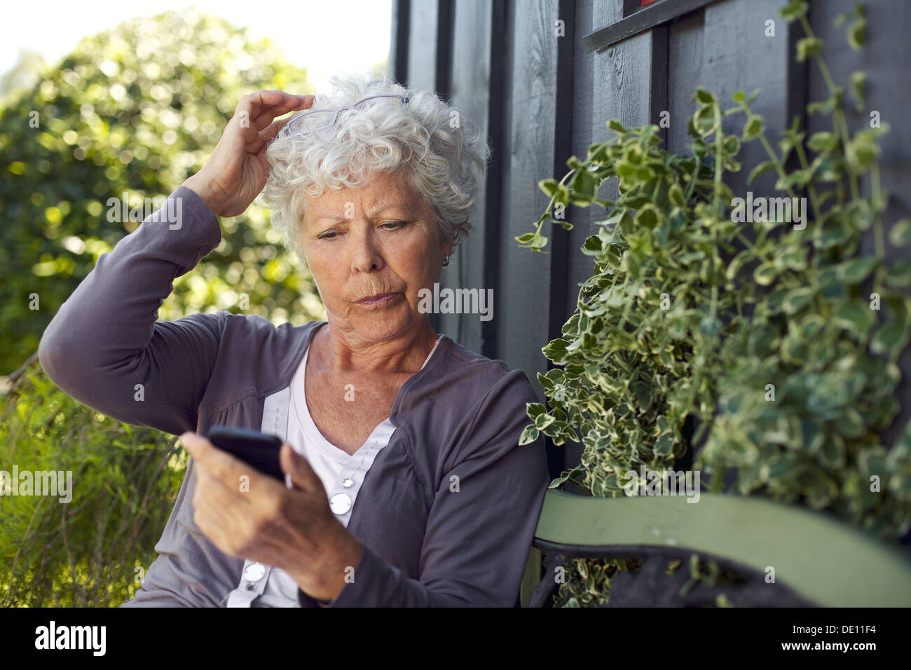 Elder woman sitting on a bench in her backyard reading text message on her mobile phone Stock Photo