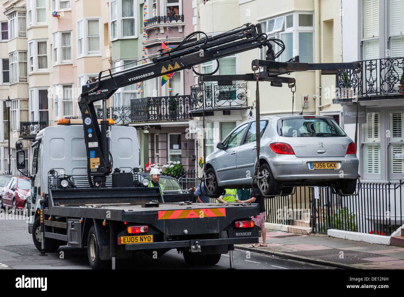 England, East Sussex, Brighton, Illegally Parked Cars being Removed from Street - Stock Image