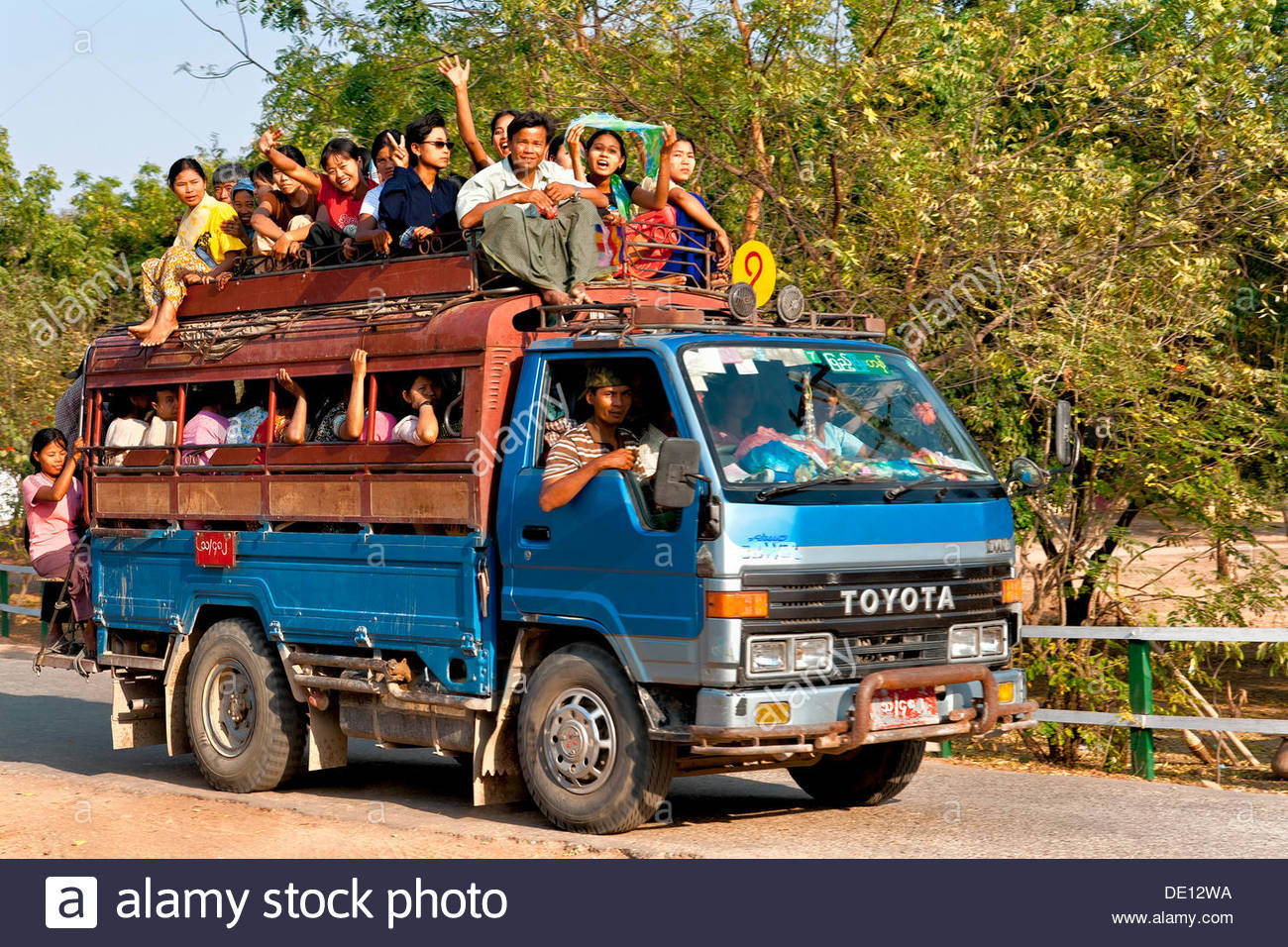 https://c8.alamy.com/comp/DE12WA/small-truck-or-bus-full-of-people-myanmar-burma-southeast-asia-asia-DE12WA.jpg