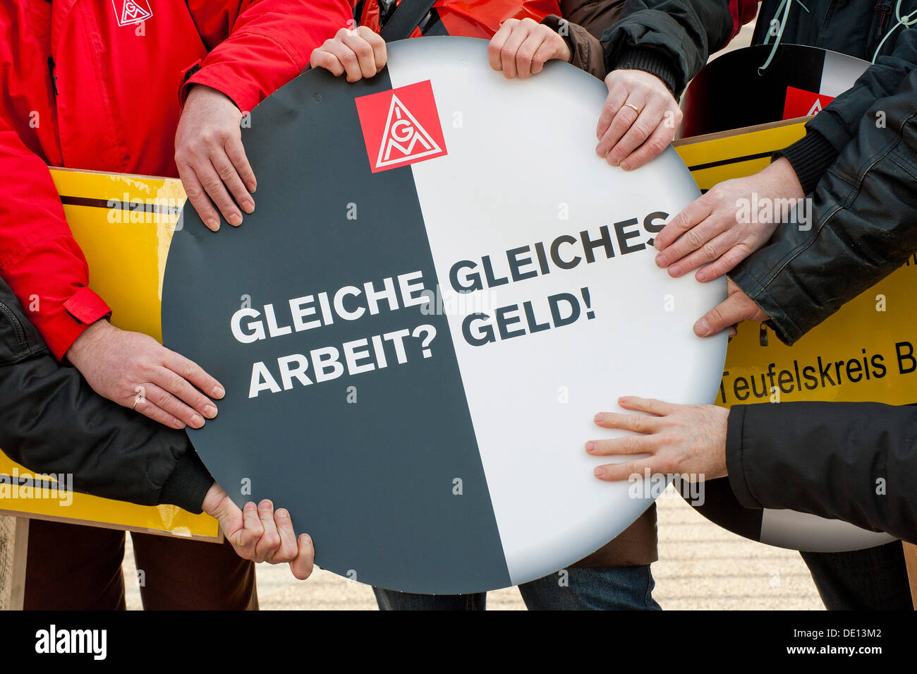 Hands holding sign: 'Gleiche Arbeit? Gleiches Geld!', German for 'Same work? Equal pay!', action day against temporary - Stock Image