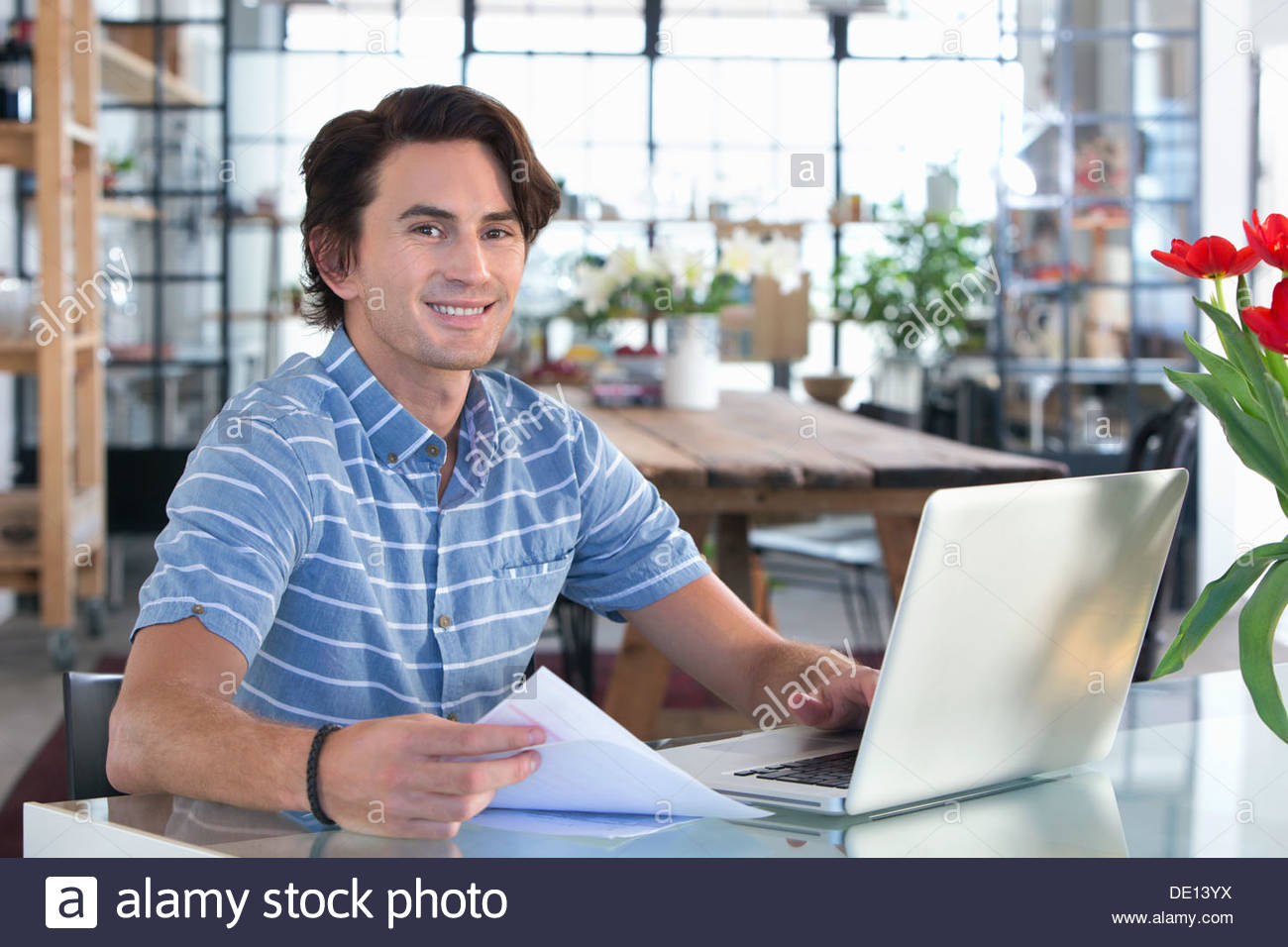 Portrait of smiling man holding paperwork and using laptop at kitchen table - Stock Image
