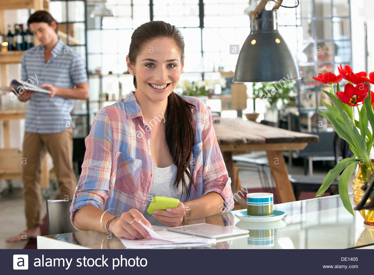 Portrait of smiling woman with cell phone and paperwork at kitchen table - Stock Image