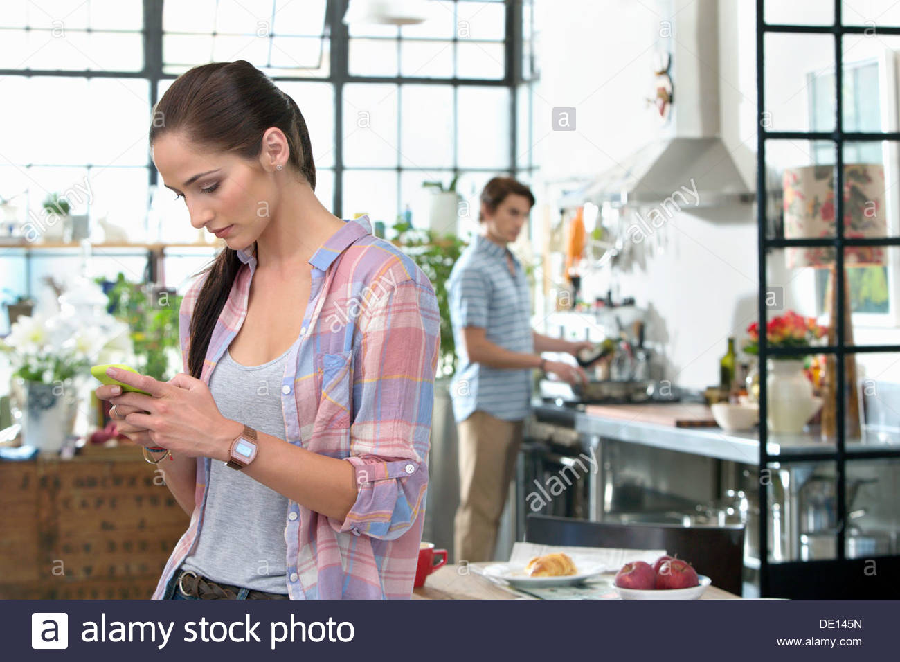 Woman text messaging with cell phone in kitchen - Stock Image