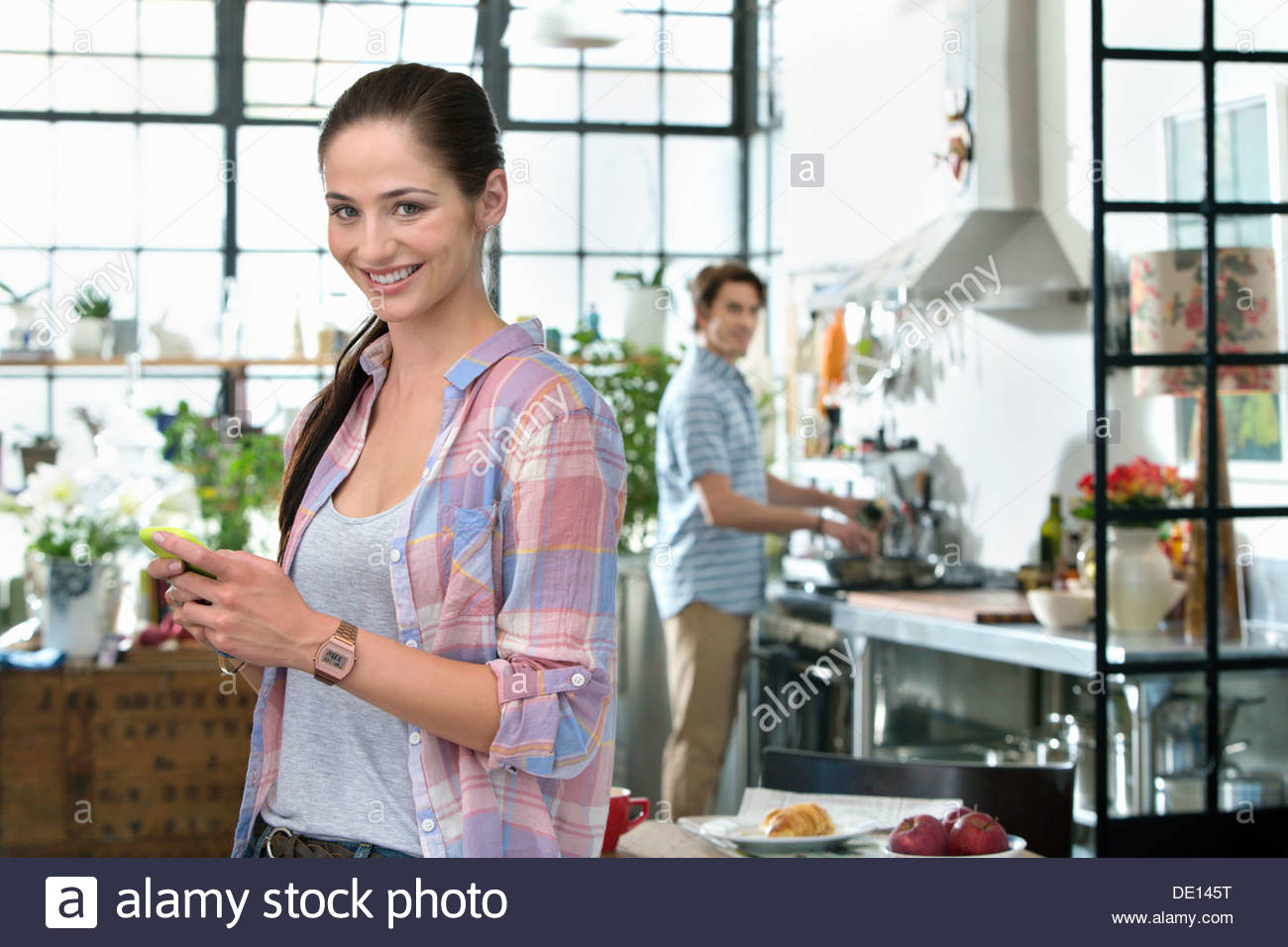 Portrait of smiling woman text messaging with cell phone in kitchen - Stock Image