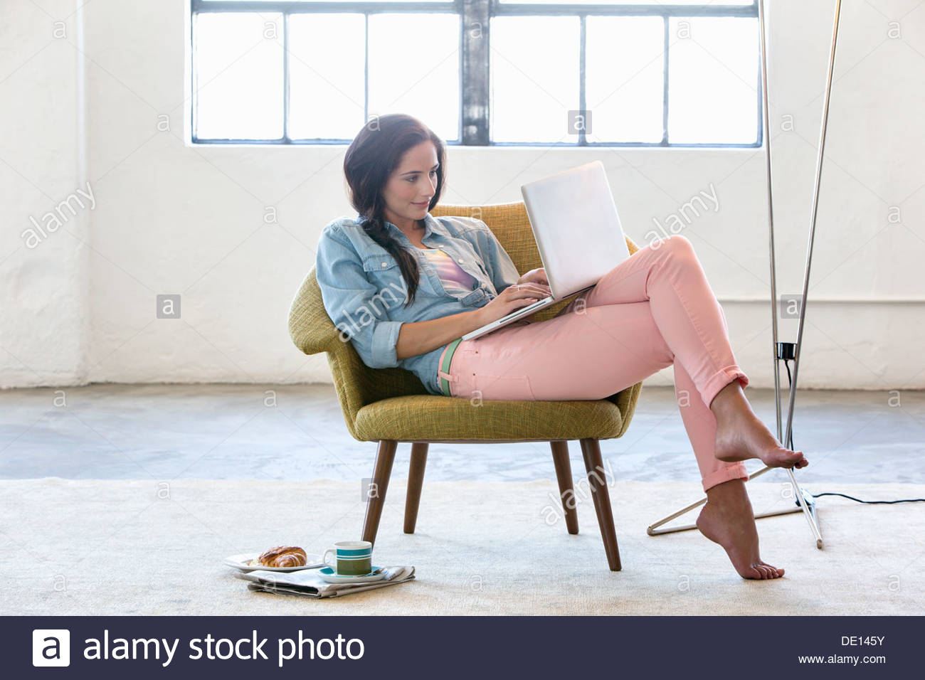 Woman using laptop in armchair - Stock Image