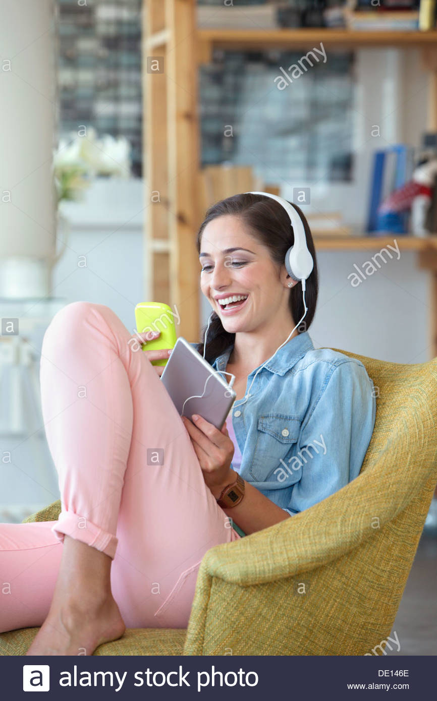Smiling woman text messaging with cell phone and listening to music on headphones with digital tablet - Stock Image