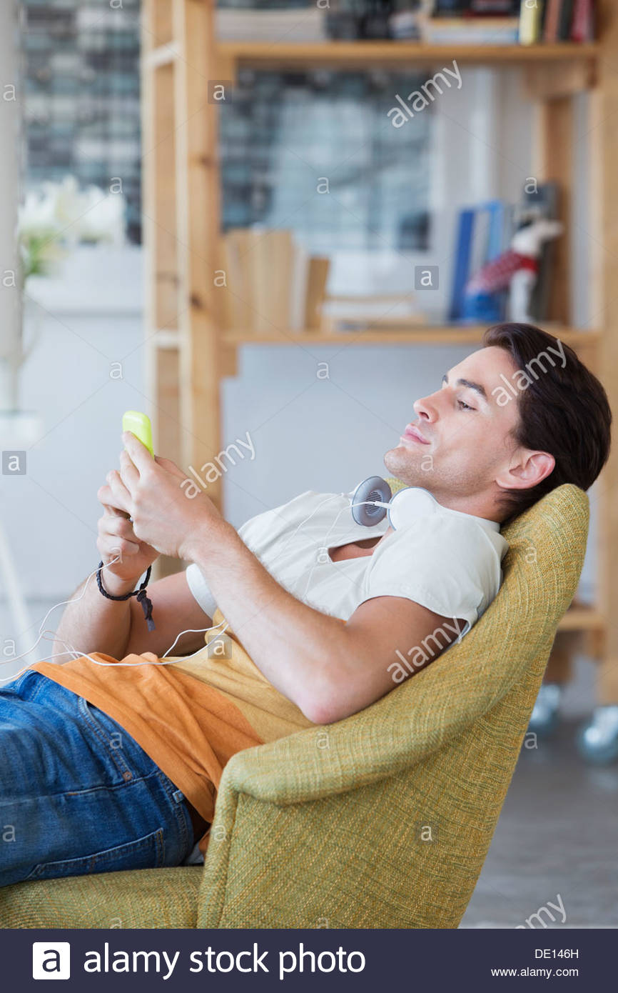 Man text messaging with cell phone in armchair - Stock Image