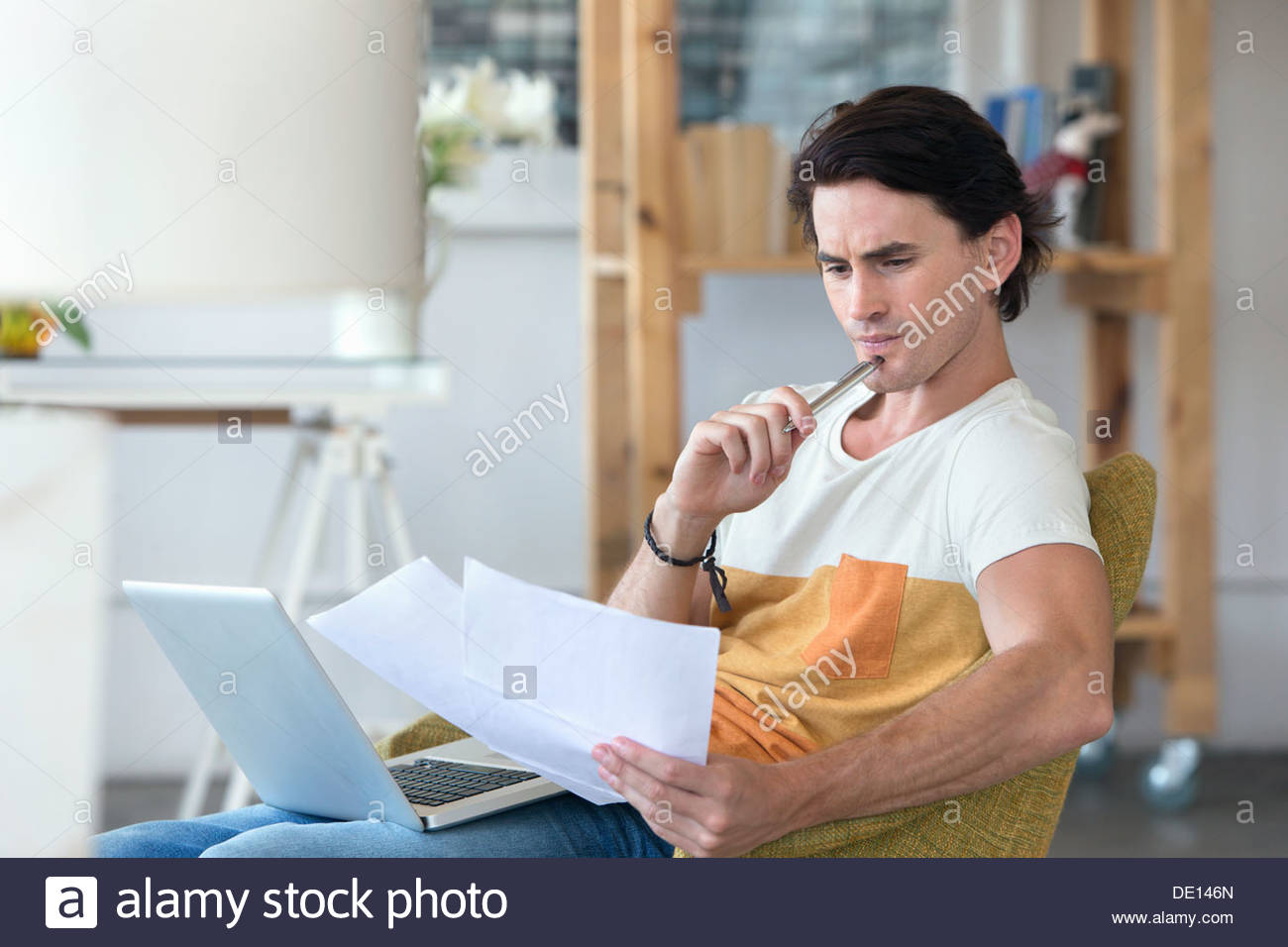 Concerned man with laptop looking down at paperwork in armchair - Stock Image