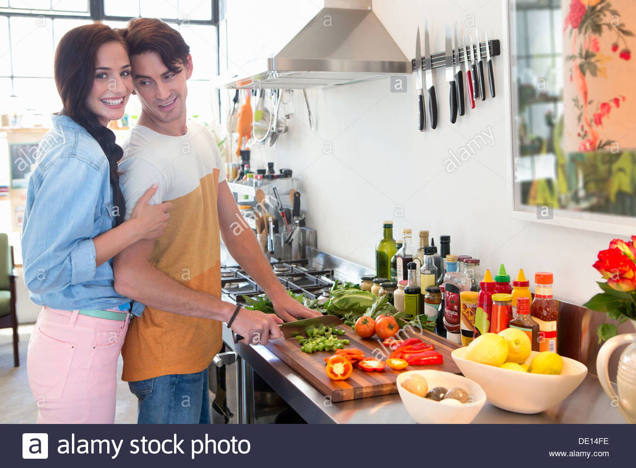 Portrait of smiling couple cooking in kitchen Stock Photo