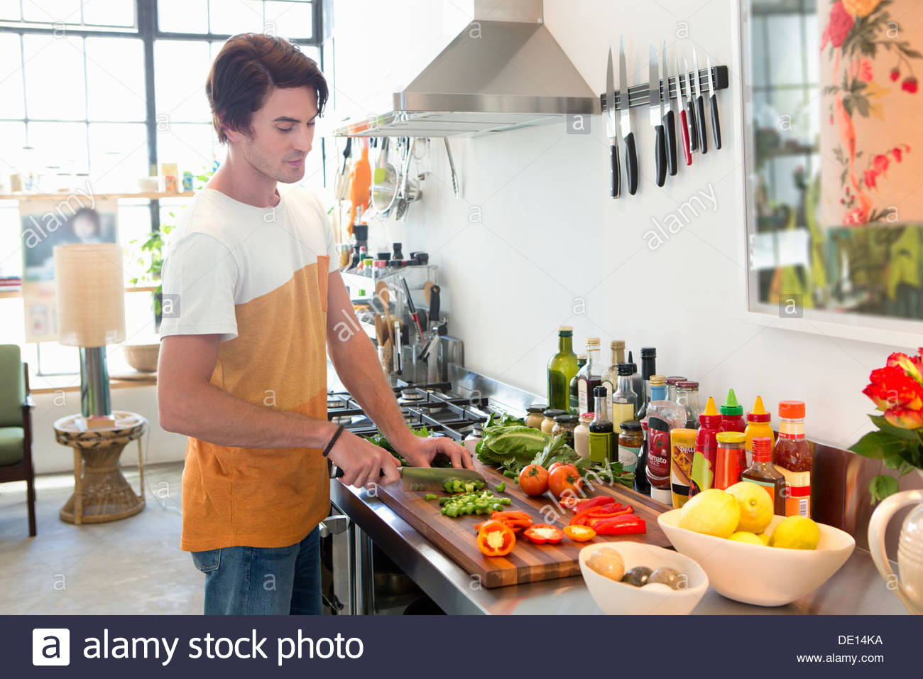 Man chopping vegetables in kitchen - Stock Image