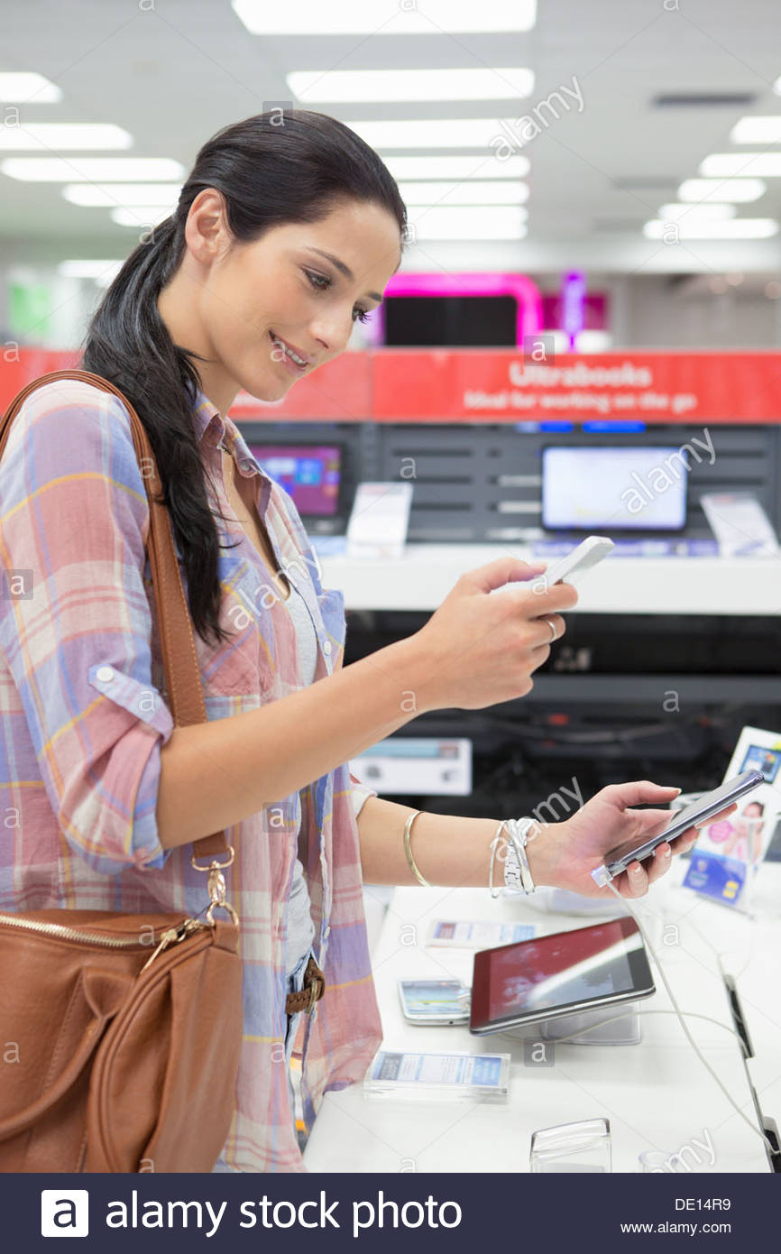 Smiling woman looking at cell phones in electronics store - Stock Image