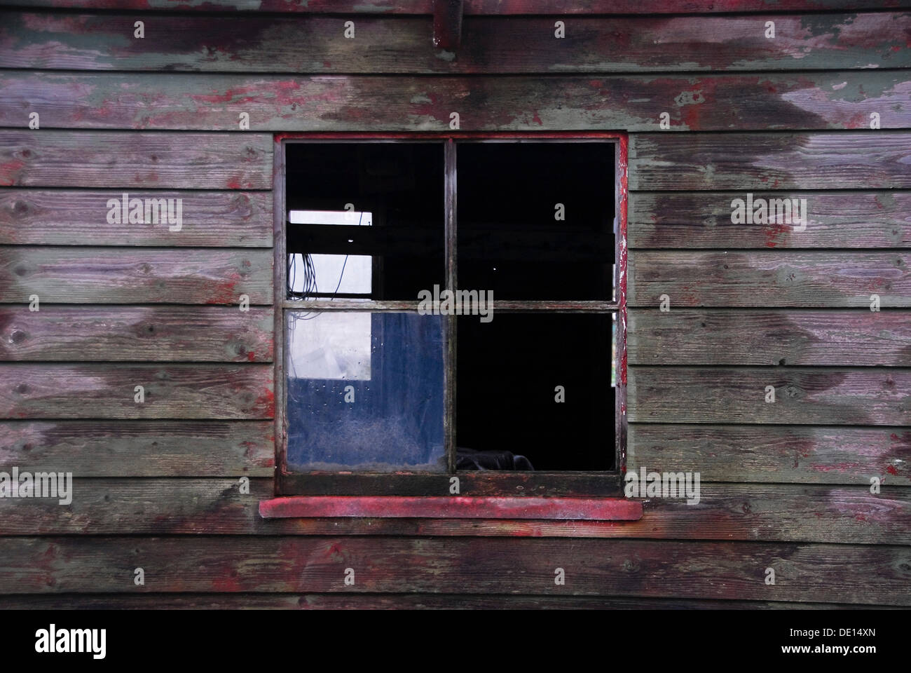 Old window with missing glass panels on a wooden shed - Stock Image