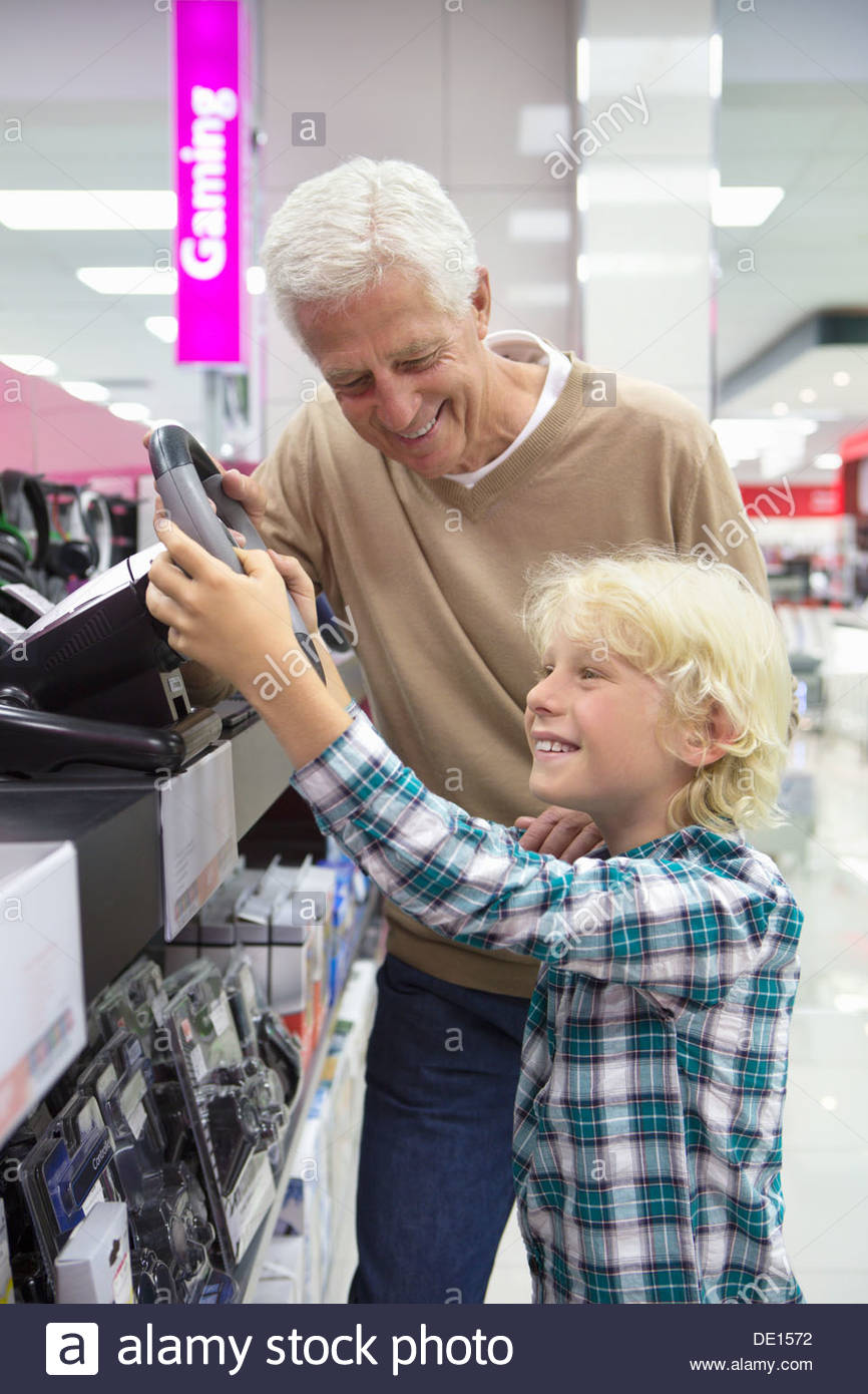 Grandfather watching grandson play with video game steering wheel in electronics store - Stock Image