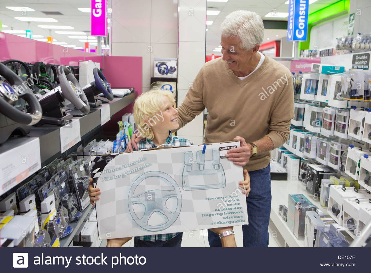Smiling grandfather and grandson holding video game box in electronics store - Stock Image