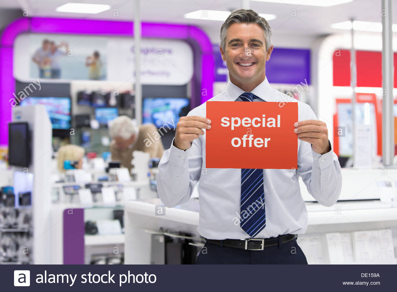 Portrait of smiling salesman holding Special Offer sign in electronics store - Stock Image