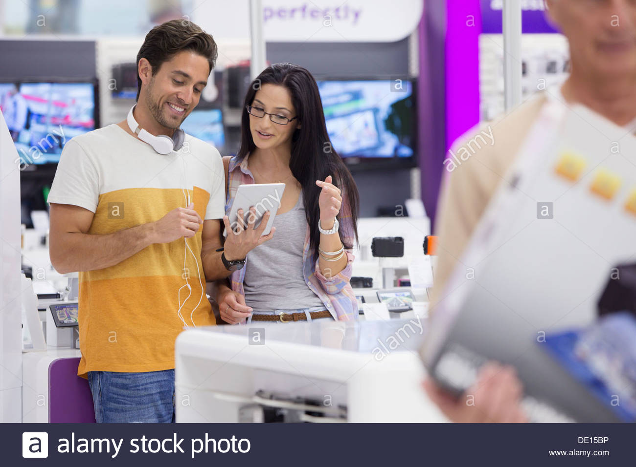 Couple looking at digital tablet in electronics store - Stock Image