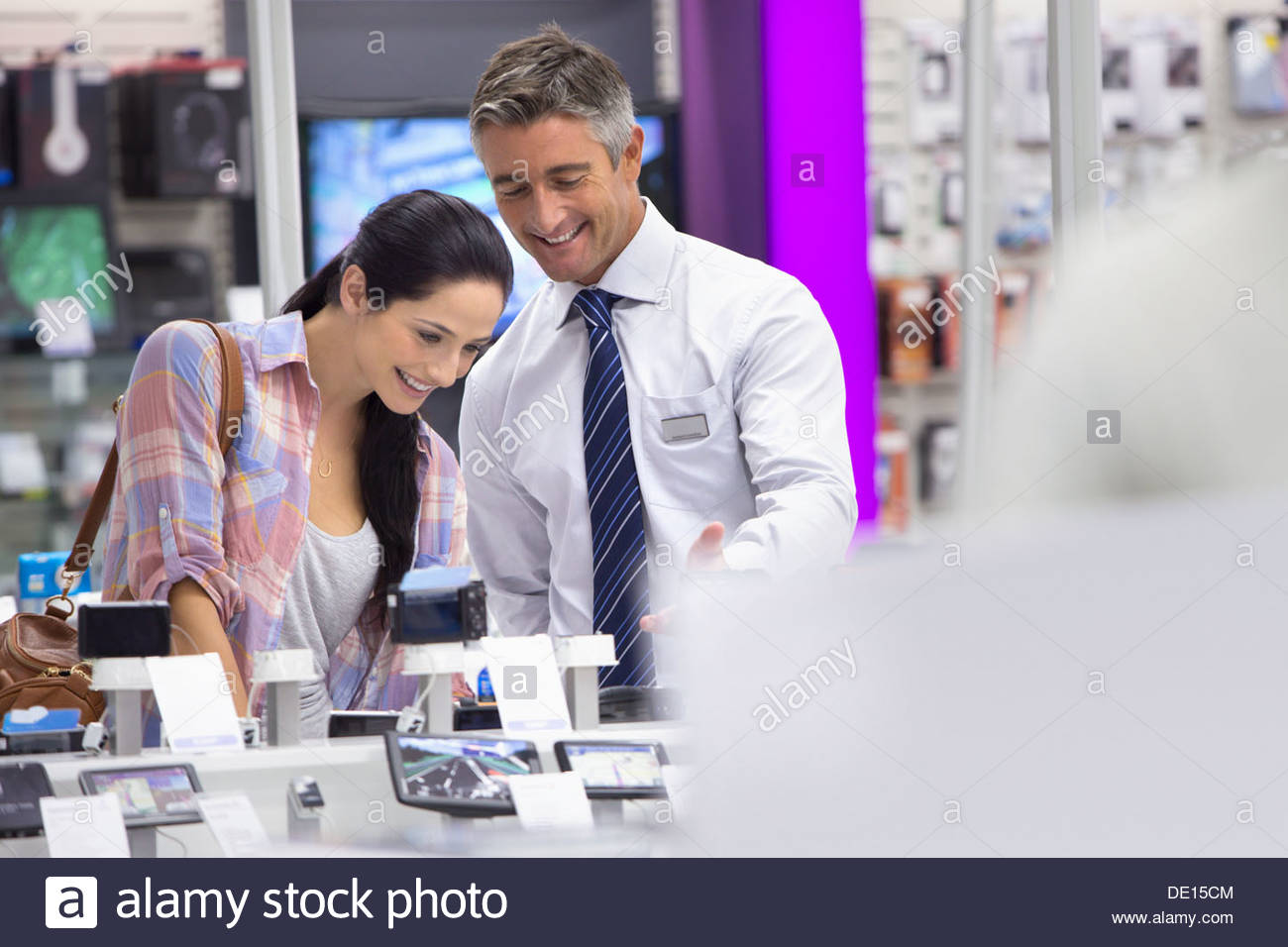 Smiling salesman showing woman digital cameras in electronics store Stock Photo