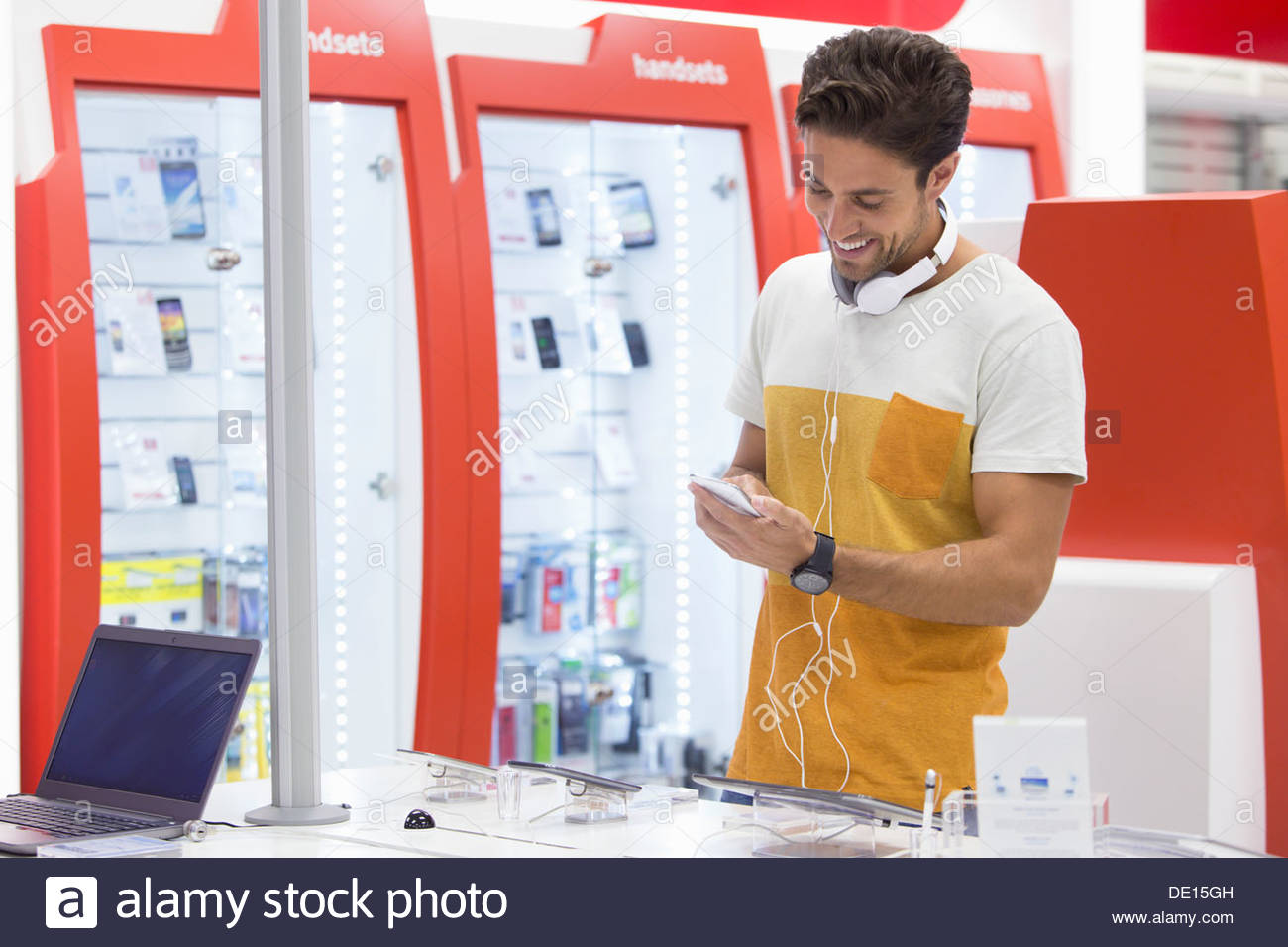 Smiling man looking at cell phone in electronics store - Stock Image