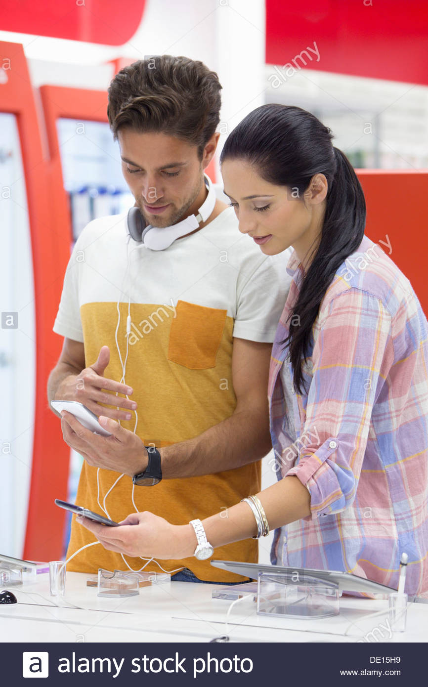 Couple looking at cell phones in electronics store - Stock Image