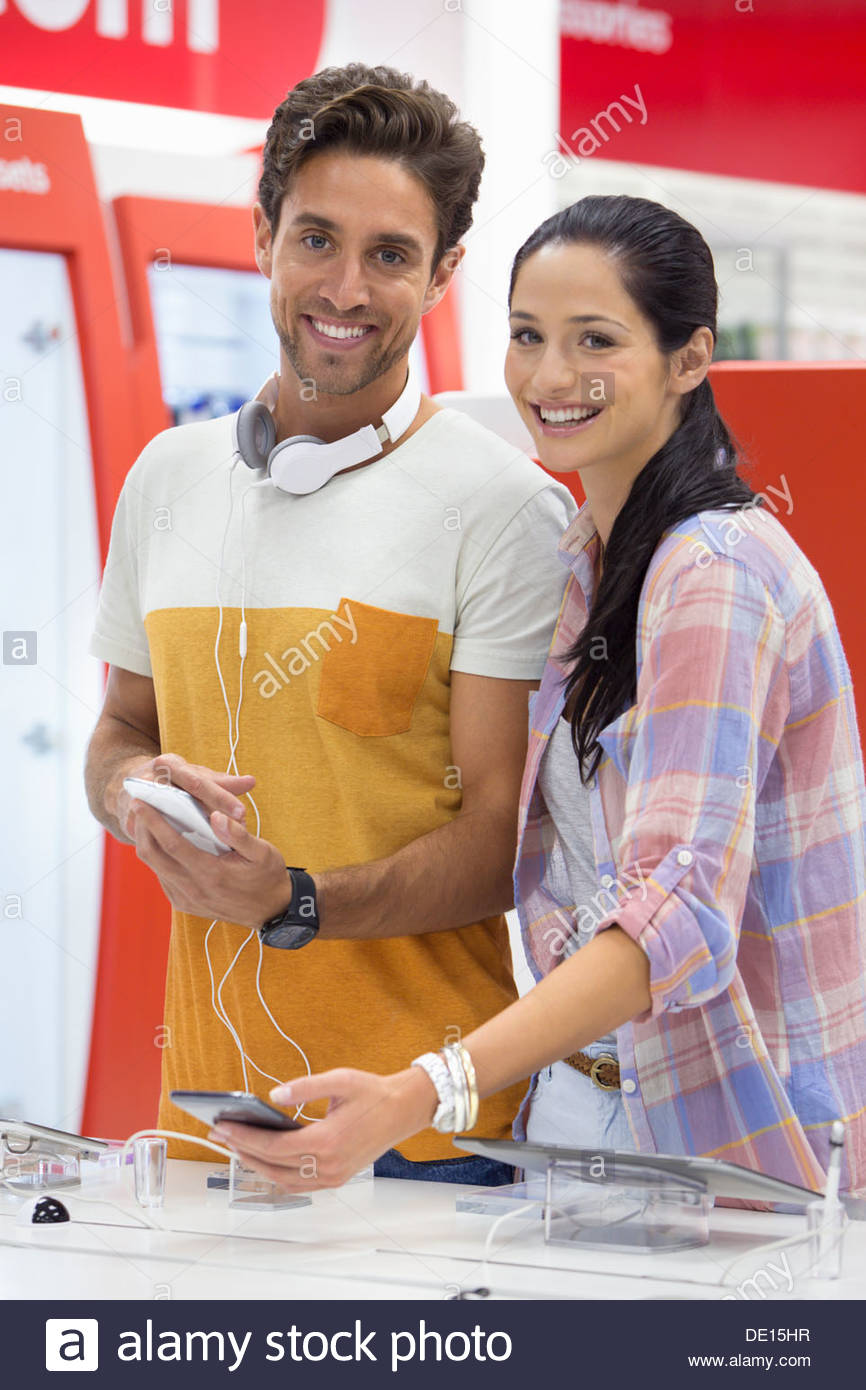 Portrait of smiling couple looking at cell phones in electronics store - Stock Image