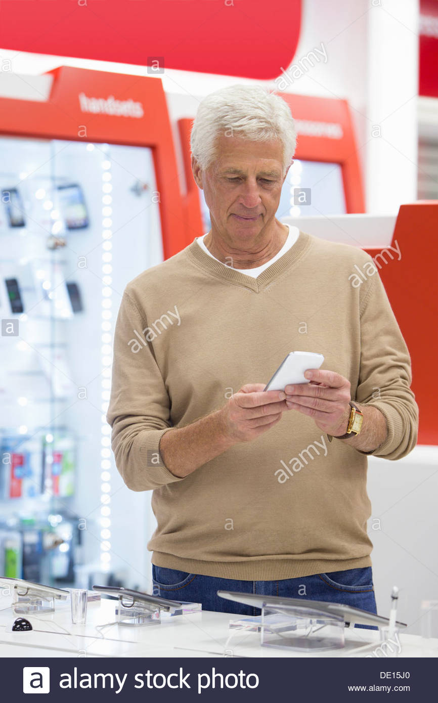 Senior man looking at cell phone in electronics store - Stock Image