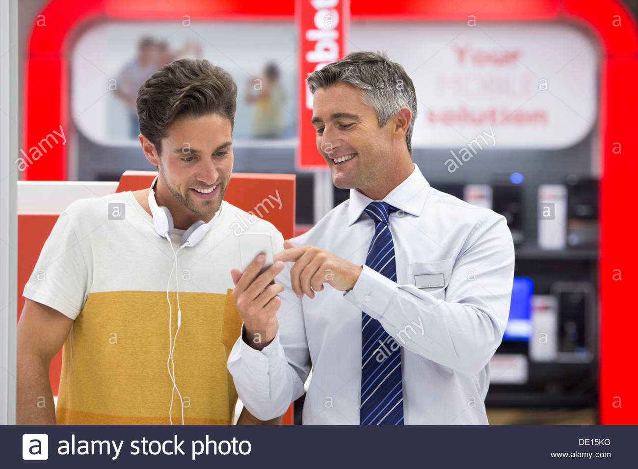 Smiling salesman showing man cell phone in electronics store - Stock Image