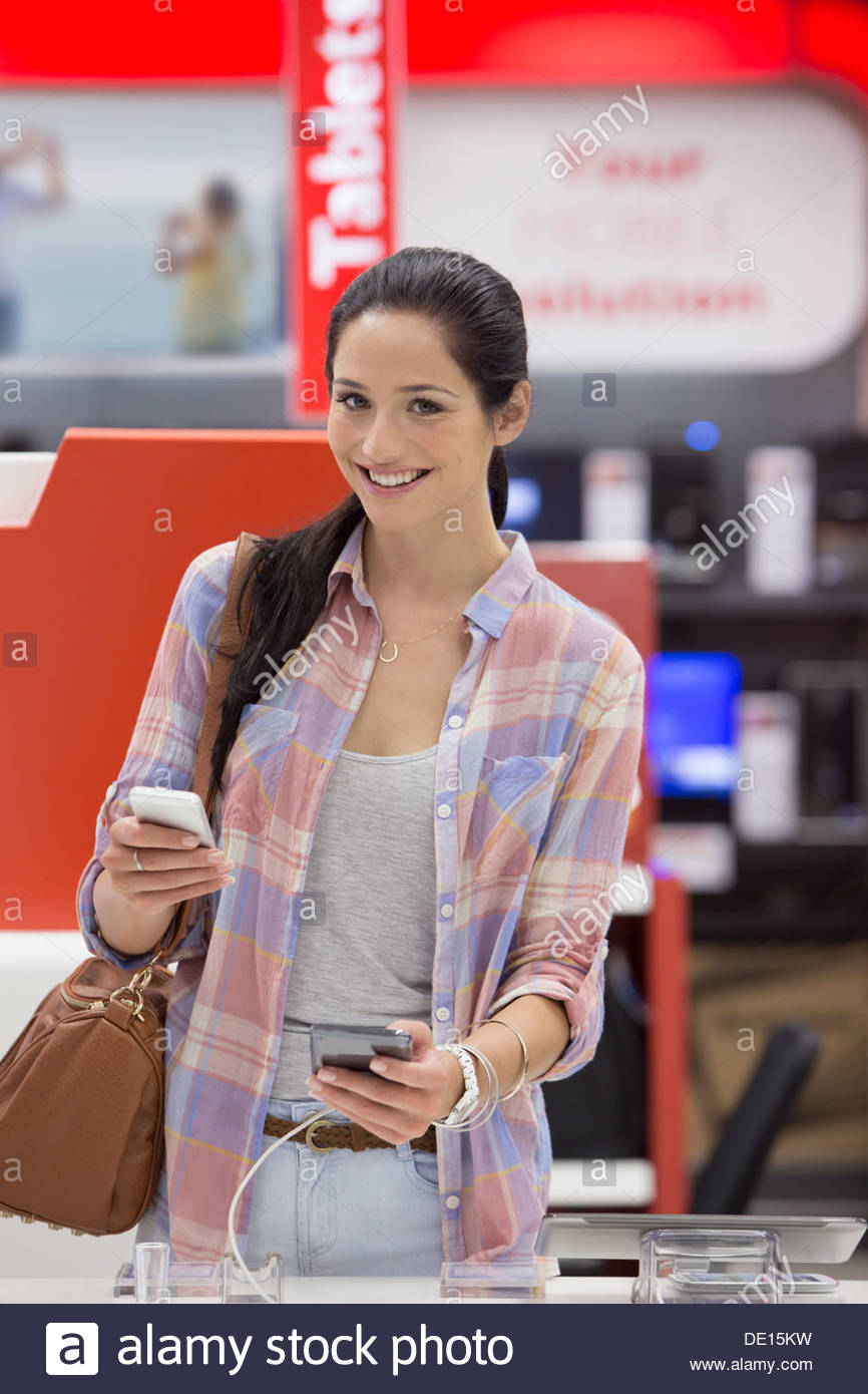 Portrait of smiling woman looking at cell phones in electronics store - Stock Image