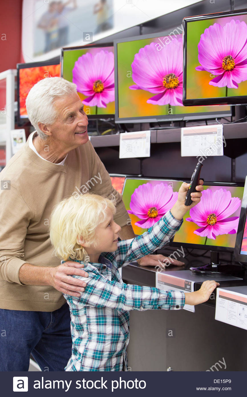 Grandfather and grandson with remote control looking at televisions in electronics store - Stock Image