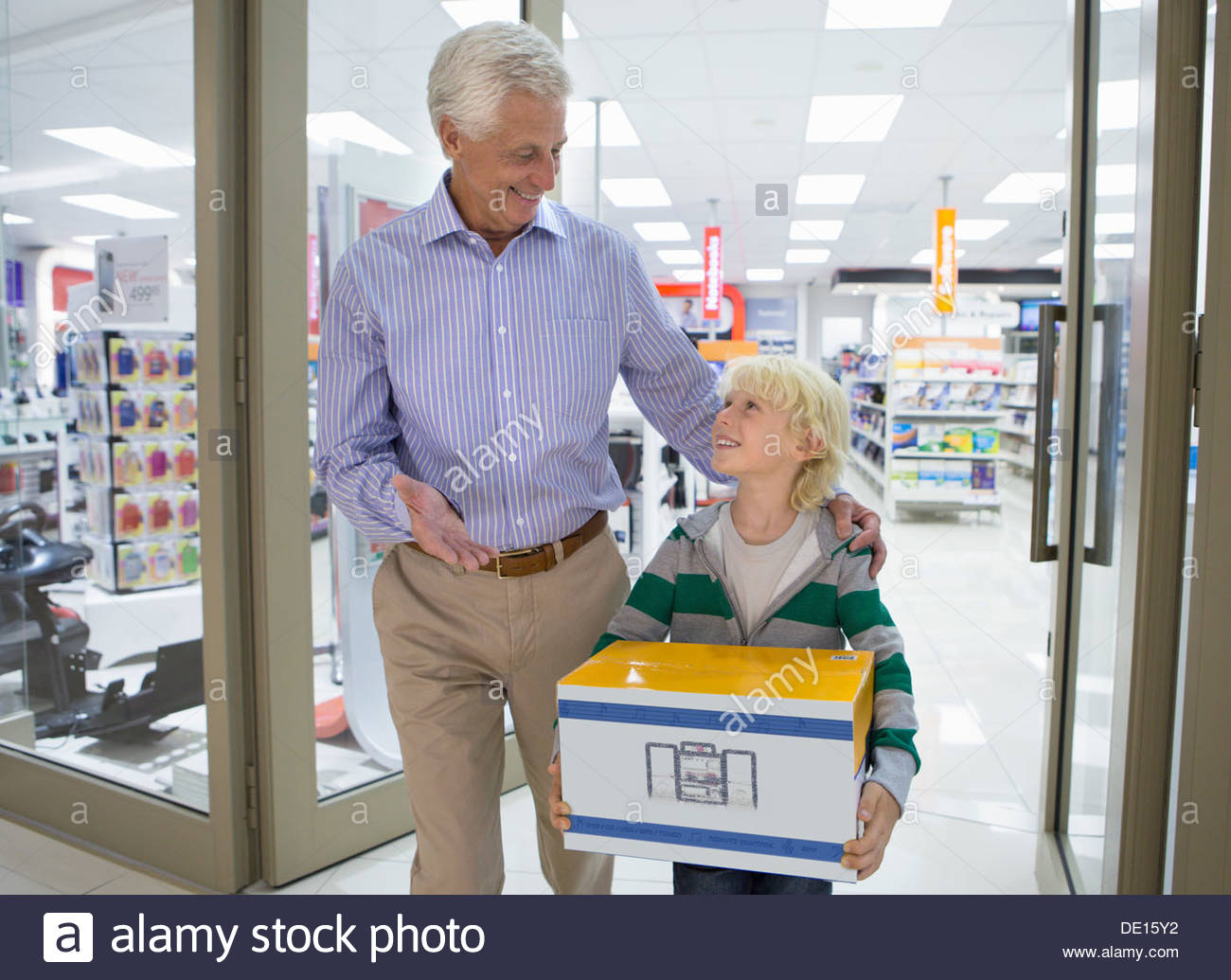 Smiling grandfather and grandson leaving electronics store with box - Stock Image