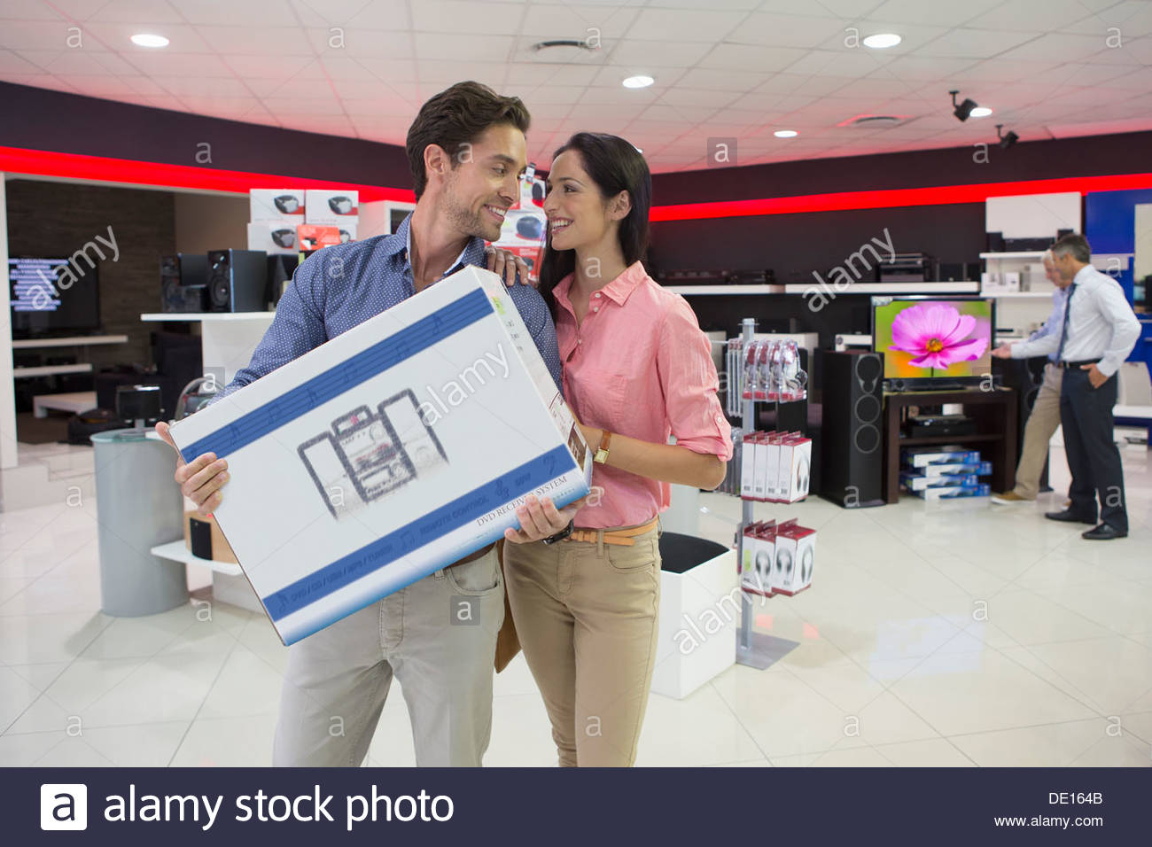 Smiling couple holding box in electronics store - Stock Image