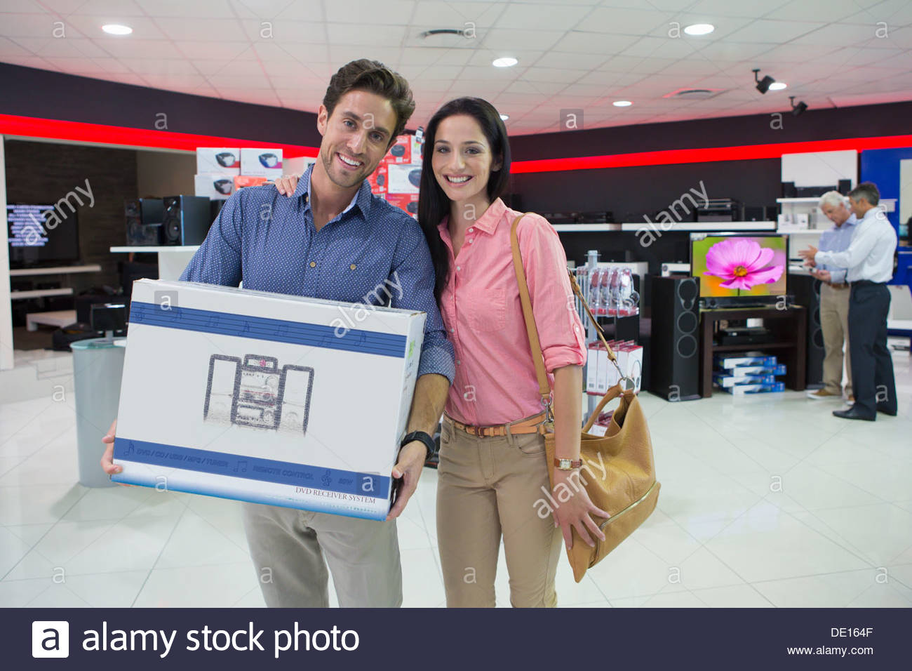 Portrait of smiling couple holding box in electronics store - Stock Image