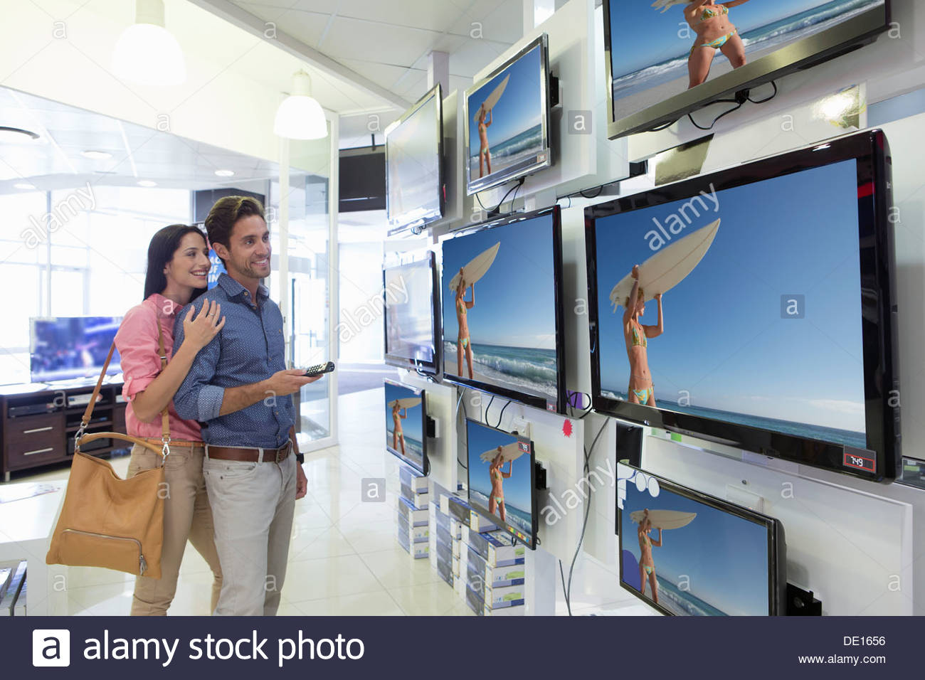 Smiling couple looking at surfer on flat screen televisions in electronics store - Stock Image